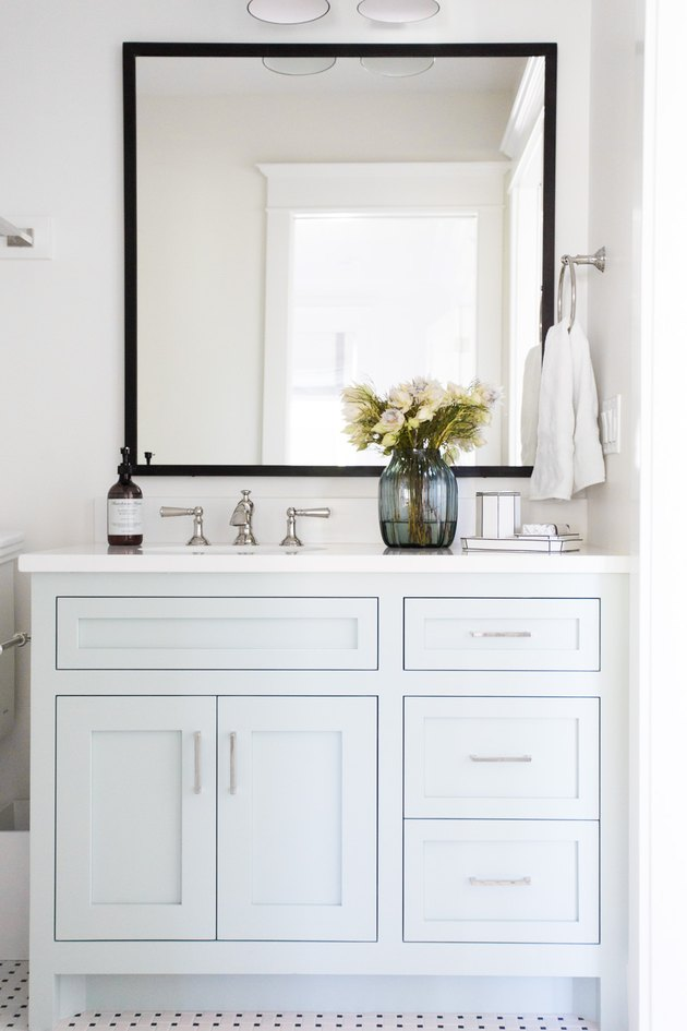 light blue bathroom cabinets with silver hardware and white countertop