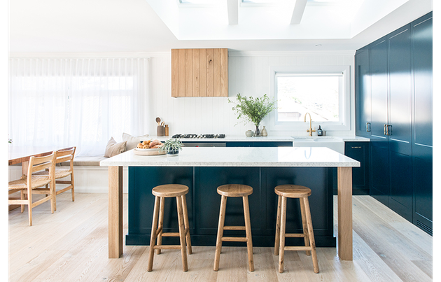 teal kitchen island with wooden stools