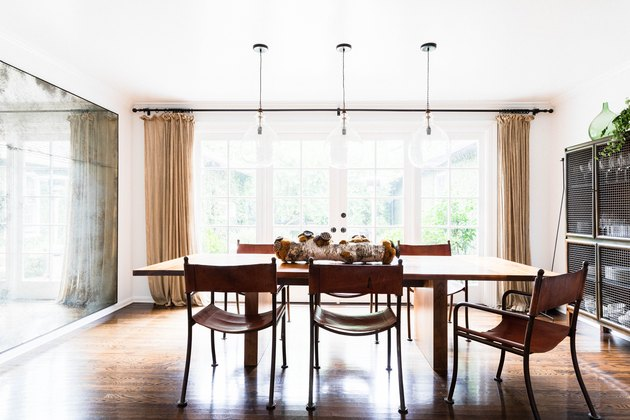 sunny dining room with glass pendant lights over wood dining table