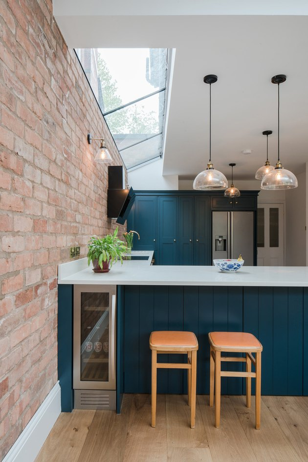 teal kitchen island with exposed brick wall
