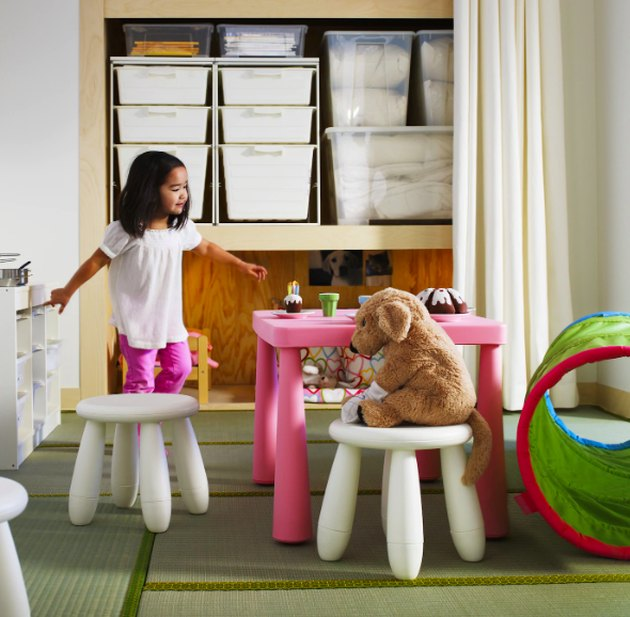 child on white stool with bear on white stool near pink table and shelves of white boxes