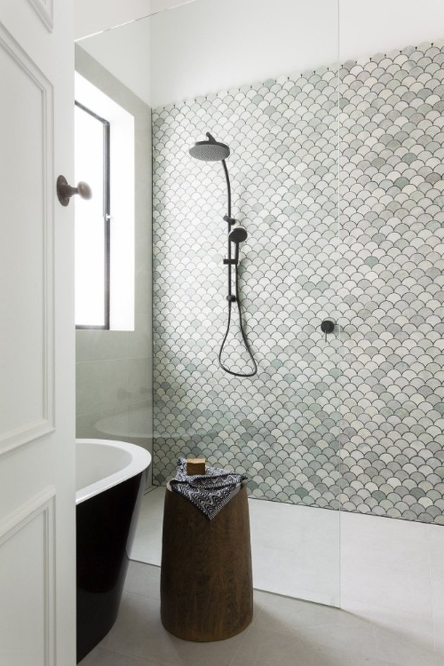 fan-shaped mosaic tile accent wall in green bathroom