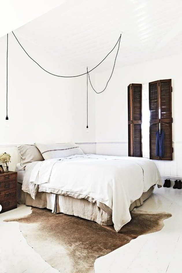 rustic bedroom with suspension lighting and wood shutters
