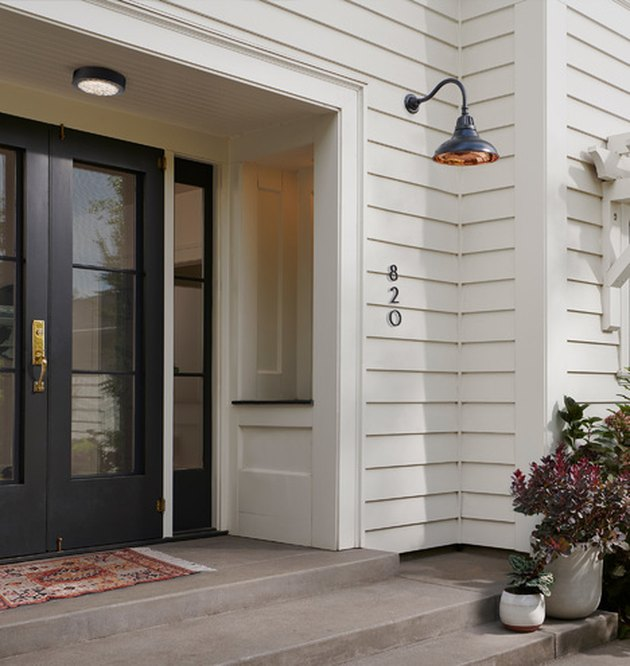 farmhouse style exterior with black glass doors and shiplap wall
