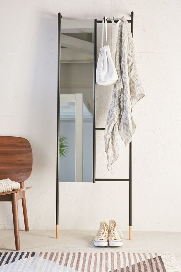 Leaning bedroom mirror from urban outfitters with accessories hanging from the rack side next to accent chair