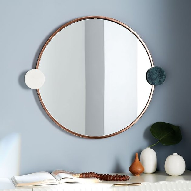 round brass mirror with marble accents