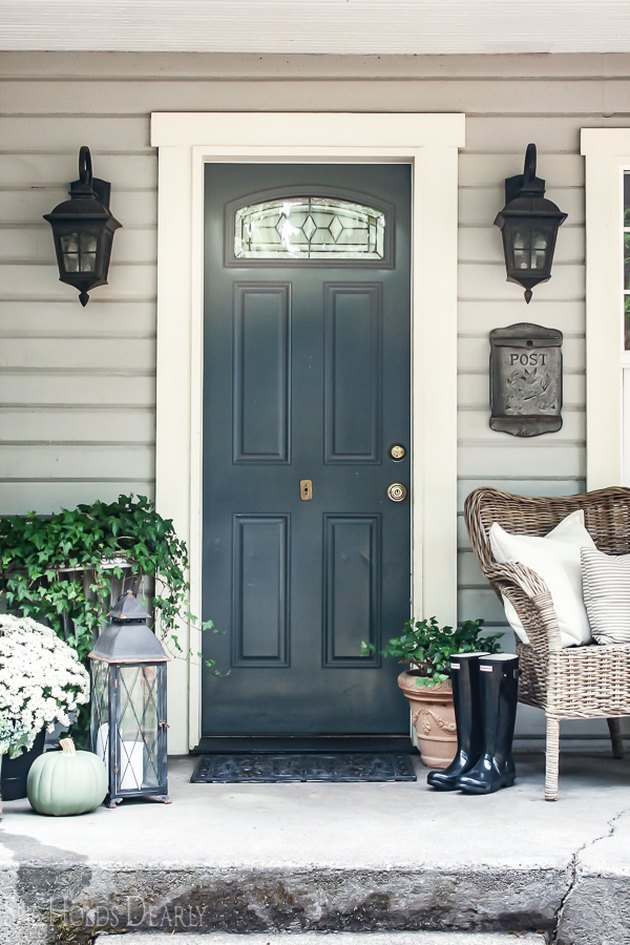 farmhouse style front porch with neutral door, plants and wicker chair