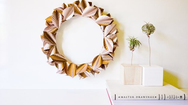 Rosegold wreath hanging on wall next to air plants.