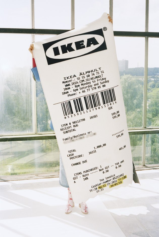 person holding a rug in the shape of an IKEA receipt