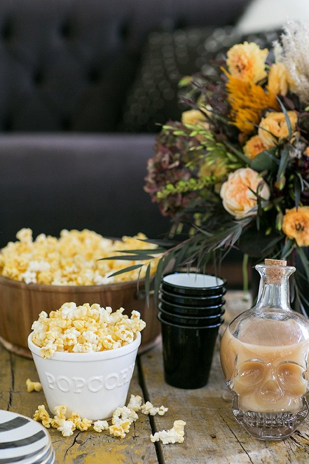 Halloween movie night party with popcorn and skull decanter