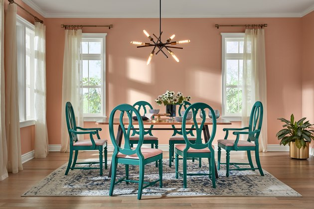 dining room space with green chairs and pink wall