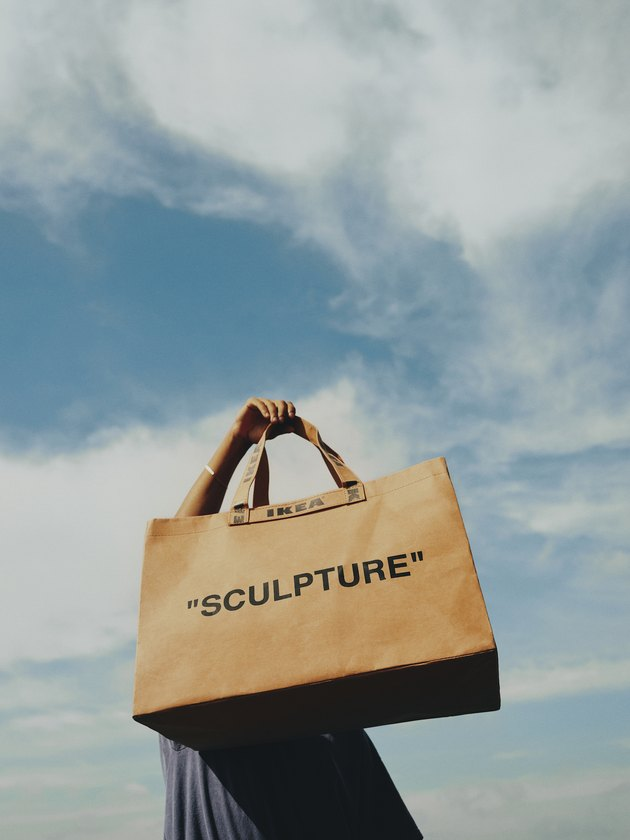 "person hold a bag with ""sculpture"" text standing outside"