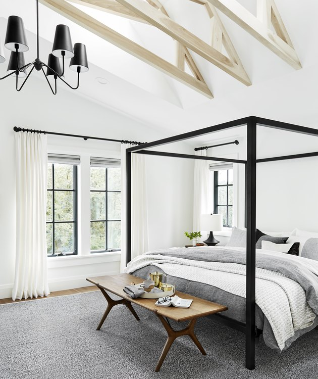Bedroom chandelier in farmhouse style space with canopy bed and gray linens