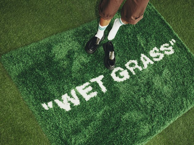 "green rug with ""wet grass"" text and person standing on top"