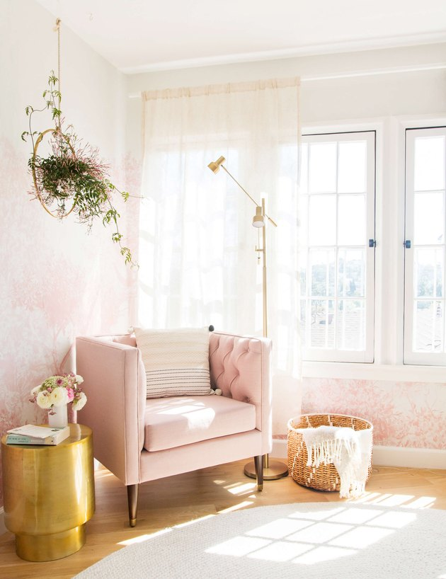 pink living room with wallpaper and velvet lounge chair