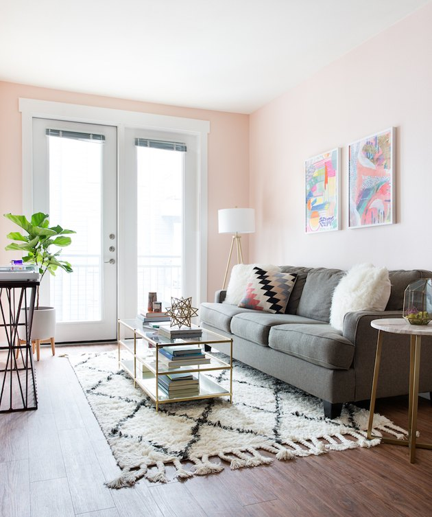 pink living room with gray sofa and white accents