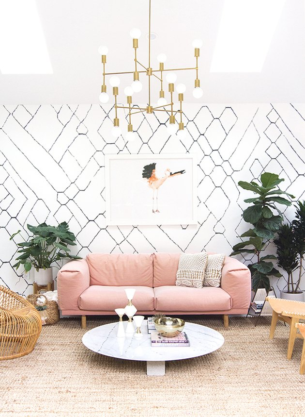 living room with comfy pink sofa and pattern wallpaper