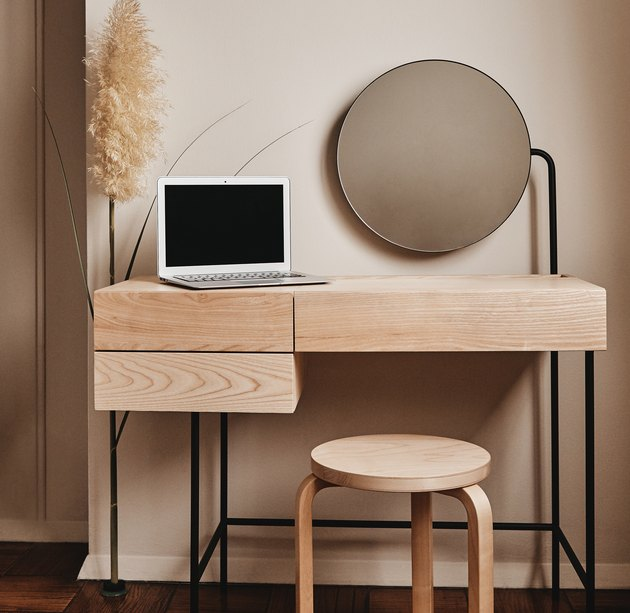 table with computer, mirror and stool nearby
