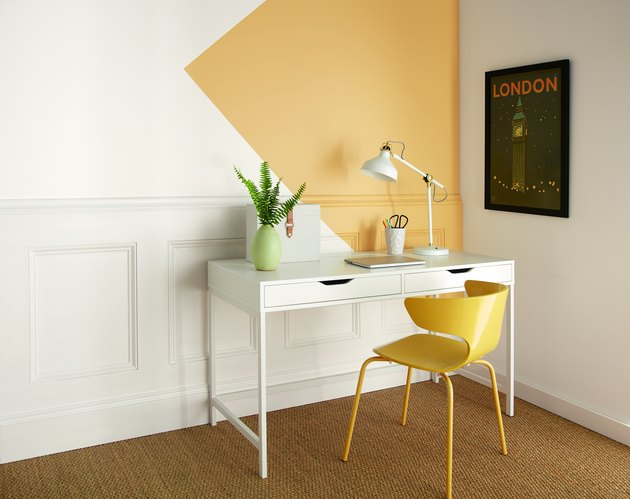 desk area with yellow chair and yellow and white wall