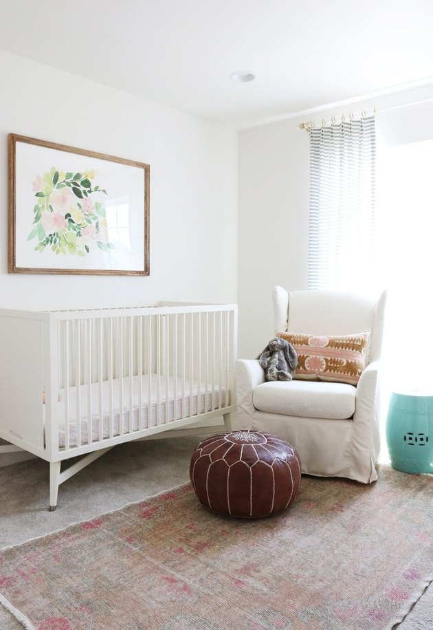 white, pink, and brown nursery idea with upholstered rocking chair and artwork above crib