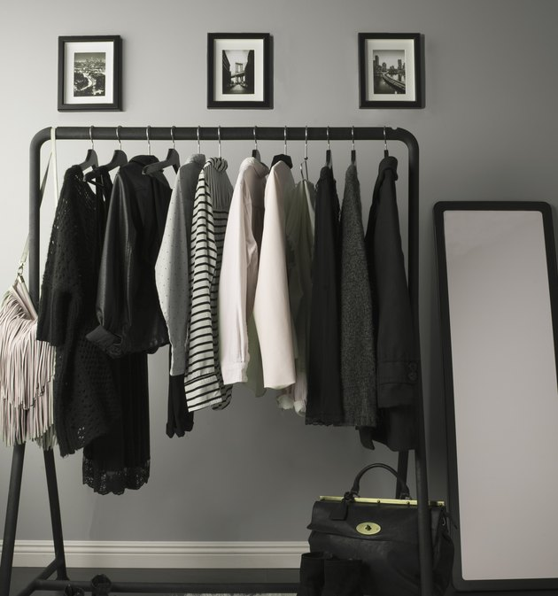 clothes rack with mirror and photographs nearby against gray wall