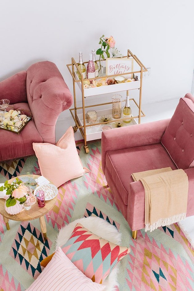 pink living room with velvet lounge chairs and bar cart