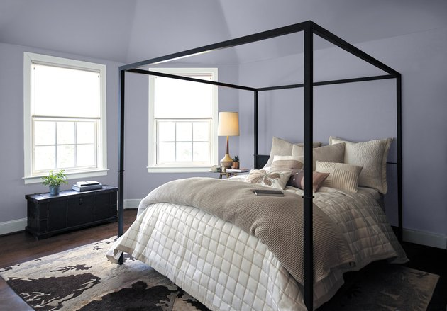 bedroom with black bed frame and pastel purple walls