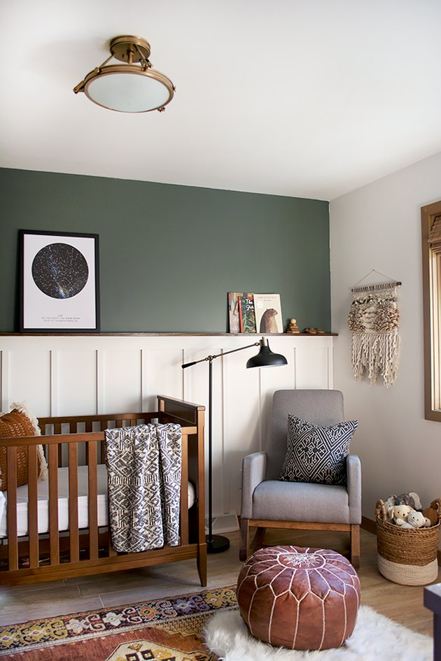 dark green, brown, and white nursery idea with wood crib and rocker in corner with floor lamp