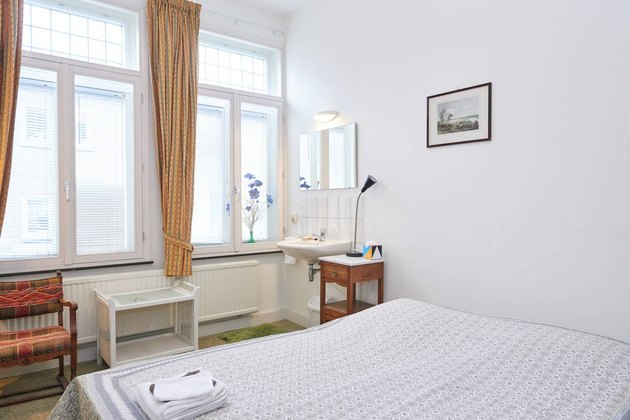 room with white bed and large windows in Maastricht