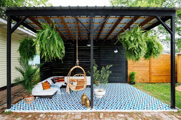 Black and galvanized metal contemporary pergola with hanging ferns and blue floor tiles