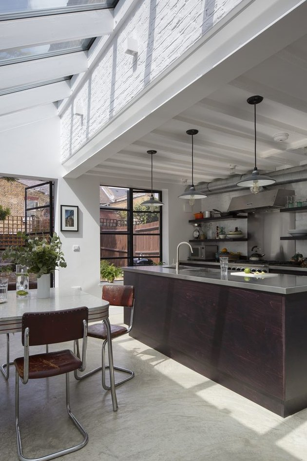 Stainless steel counters, cement floors and exposed ductwork in this industrial style kitchen