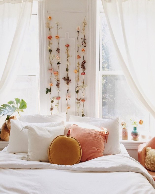 bedroom with dried flowers hanging above the bed
