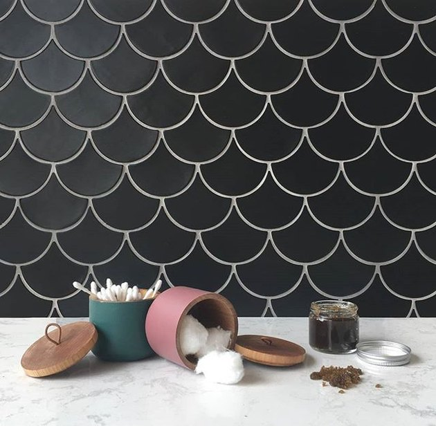 black ceramic tile in fish scale pattern on bathroom wall