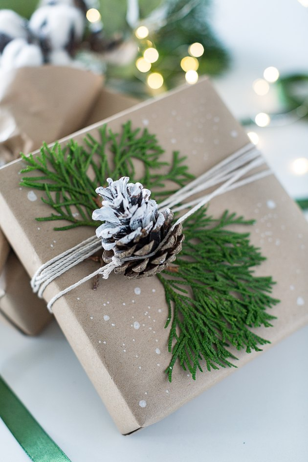 Present wrapped with brown paper and a snowy pinecone