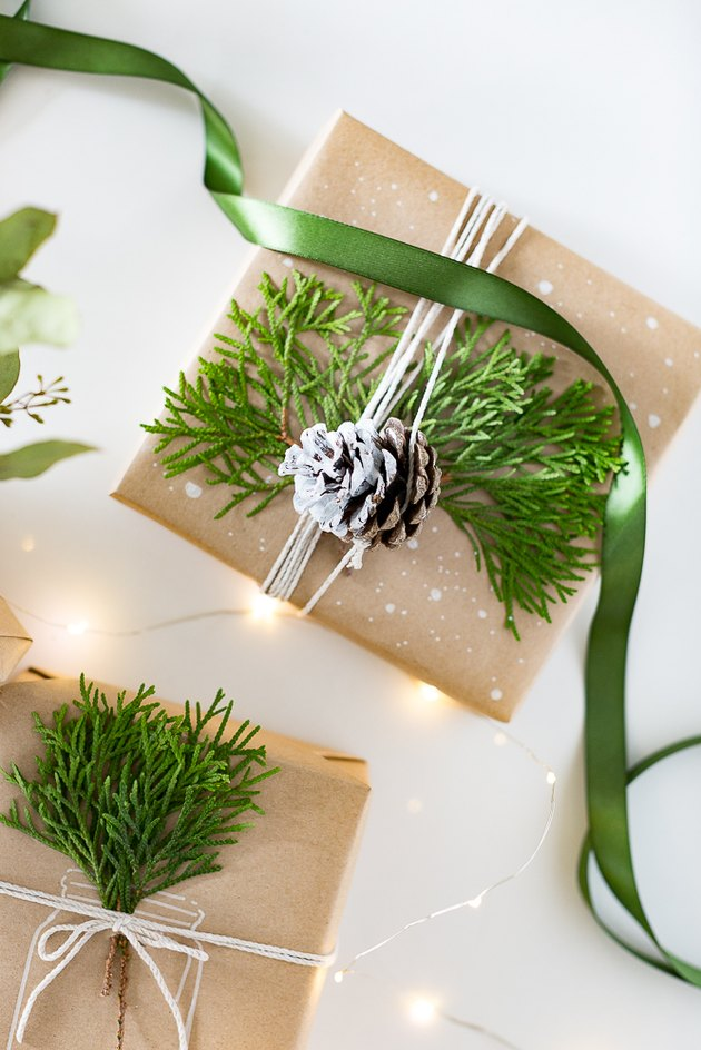 Present wrapped with brown kraft paper and faux greenery with a pinecone