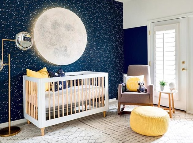 yellow nursery idea with space themed walls and floor pouf by rocking chair