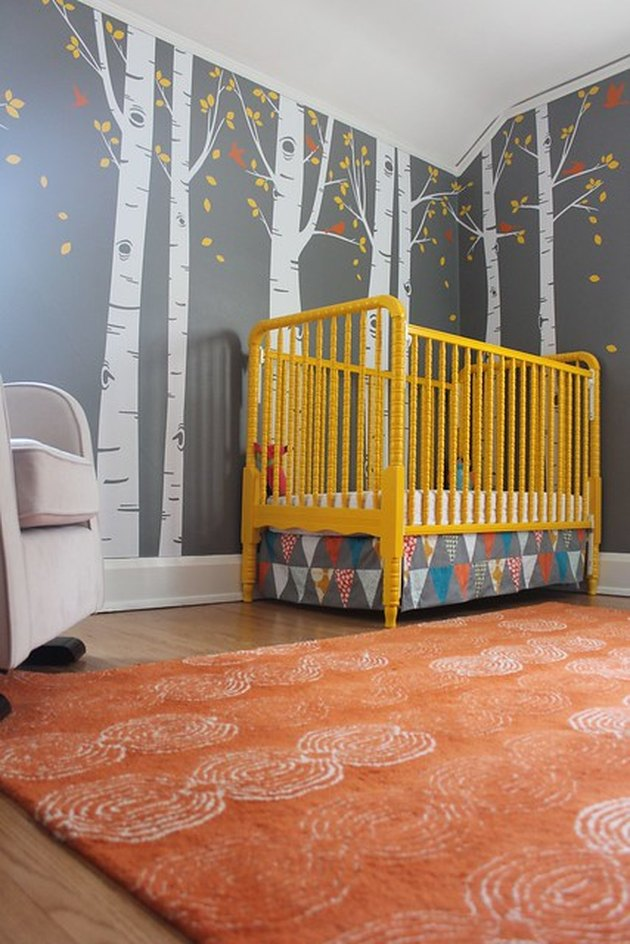 yellow nursery idea with vibrant crib and rust area rug and gray wallpaper