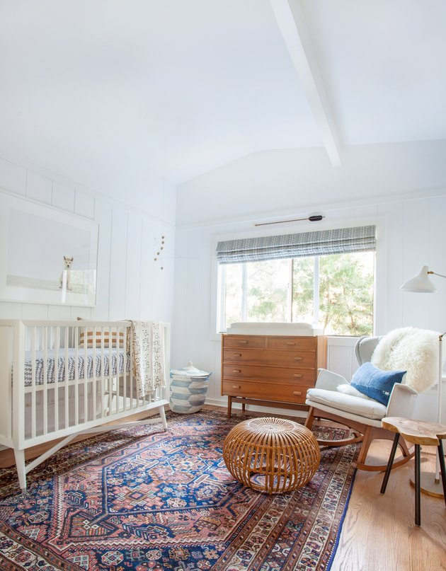 bohemian baby nursery idea with blue and pink kilim rug with lots of wood elements and sheepskin throw