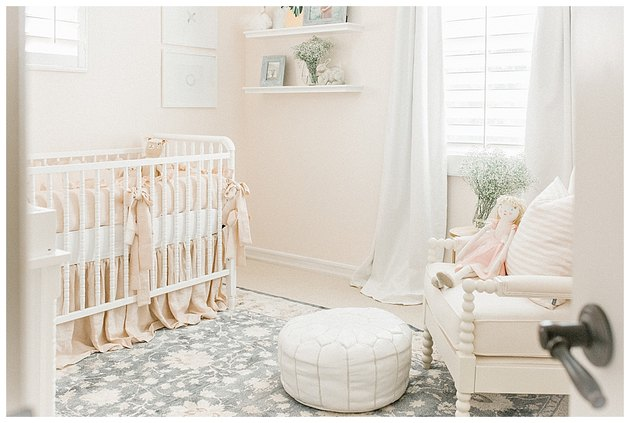 vintage blush pink nursery idea with traditional style crib and floating shelving