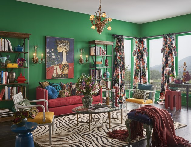 living room space with green walls, red couch, and open shelves