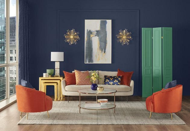 living room with navy blue wall, white couch, and orange chairs