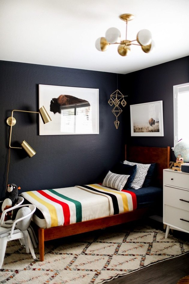 Midcentury kids' bedroom idea with globe-style ceiling light, navy blue walls, and vintage-inspired blanket