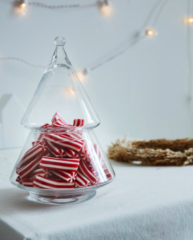 serving bowl with lid in the form of a christmas tree with red and white candies inside