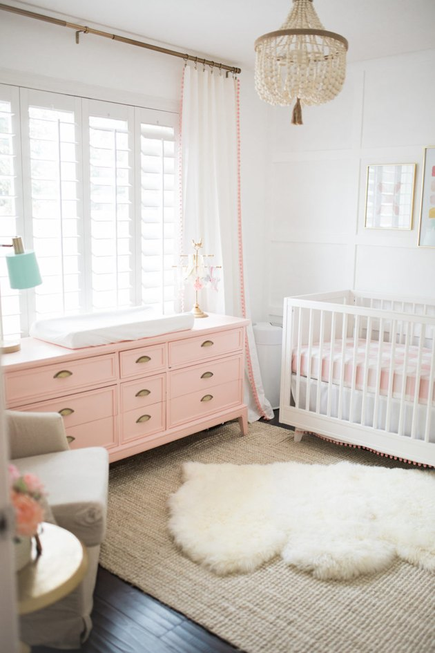 baby nursery idea with pink changing table and crib with floor to ceiling drapery