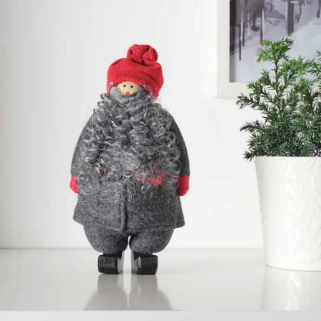 decorative item in the shape of a figure with a beard, gray clothing, and red beanie