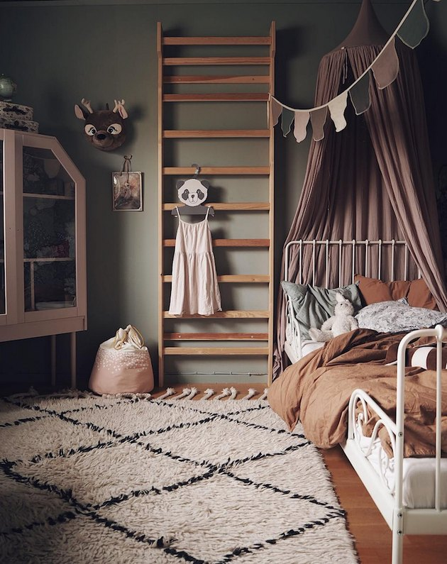 Scandinavian kids bedroom idea with pink bed canopy and wall bar