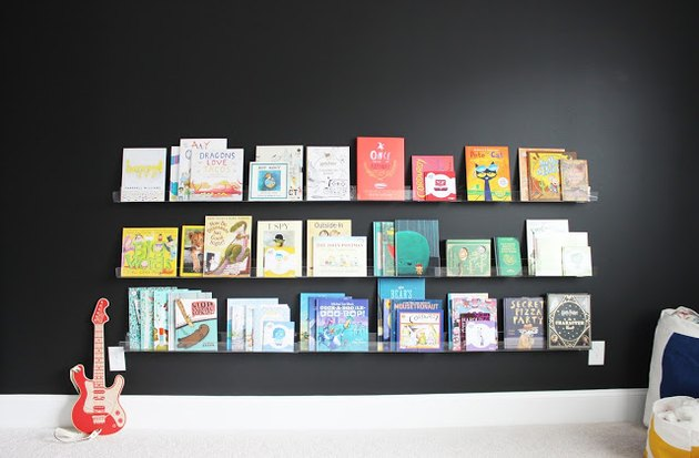 kids' bedroom idea with black walls and picture ledges displaying books