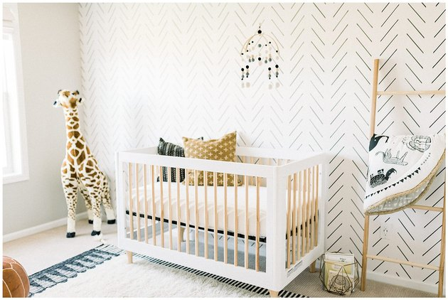 Scandinavian nursery idea with patterned wallpaper accent wall behind crib and leaning blanket rack