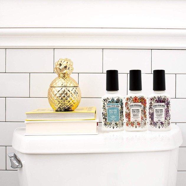 white bathroom with gold pineapple on books and three-piece Poo-Pourri bathroom spray set