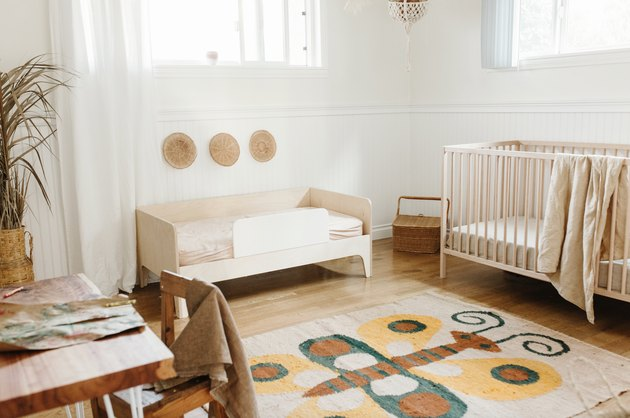 Minimal bohemian baby nursery idea with vintage butterfly rug